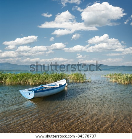 view of a rowboat and cloudscape on lake Prespa from the macedonian side - stock photo