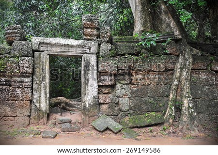 View of a Ruined Wall and Doorway at Ta Prohm at the Historic Angkor Wat Temple Complex in Cambodia - stock photo