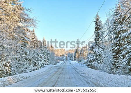 View of a rural road in Maine after a snowstorm with clear skies and snow covered road. - stock photo