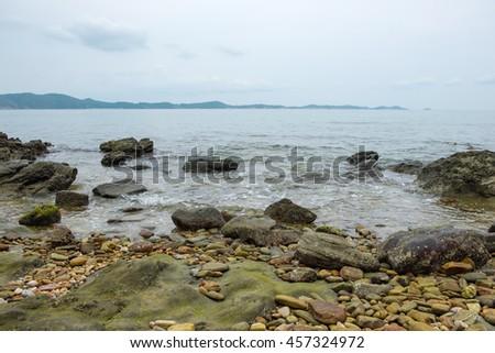 View of a sea coastline with stones and rocks at Khao Laem Ya, Mu Ko Samet National Park in Thailand. - stock photo
