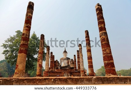 View of a seated Buddha statue among ruined columns in Wat Mahathat, an ancient Buddhist temple in Sukhothai Historical Park, Thailand ~ Beautiful scenery of a UNESCO world heritage site - stock photo
