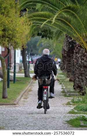 View of a senior man walking on a bicycle with is pet dog.  - stock photo