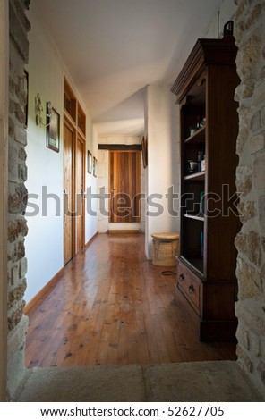 View of a shiny wooden-floored hallway in a traditional luxurious French villa, with bookcase and wicker basket. - stock photo