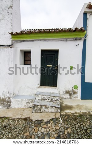 View of a small house in between two bigger houses on a street typical from the region of the Alentejo, Portugal.