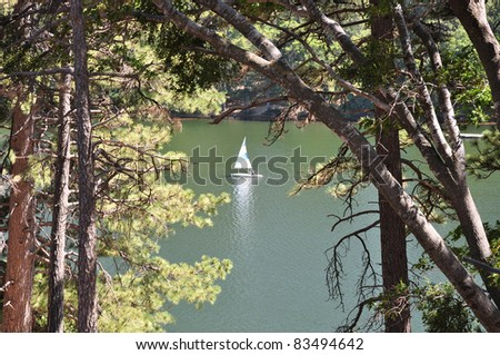 View of a small sailboat on Lake Gregory. Located in the San Bernardino mountains of Southern California. - stock photo
