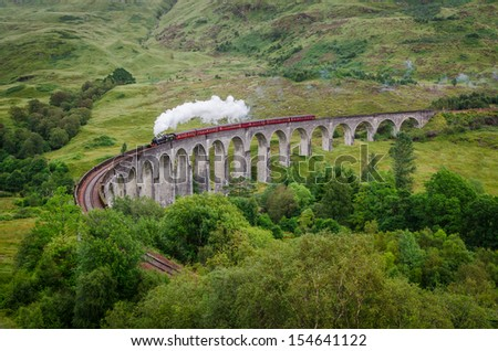 View of a steam train on a famous Glenfinnan viaduct, Scotland - stock photo