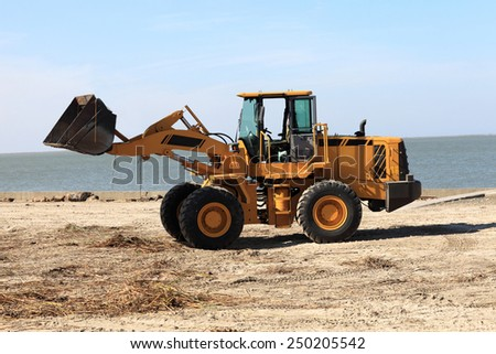 View of a tractor on the beach - stock photo