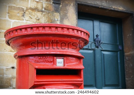 View of a Traditional British Red Post Box on a Street in an English Town - stock photo