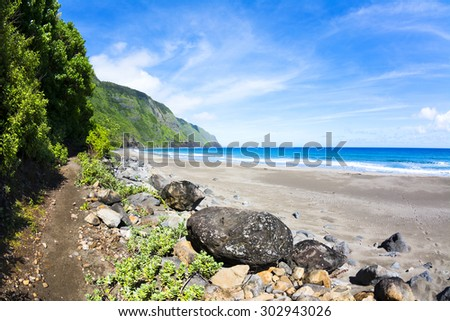 View of a tropical beach in Hawaii with a trail leading into the mountainside foliage - stock photo