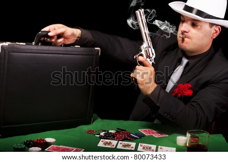 View of a white suit gangster man holding a gun and a briefcase. - stock photo