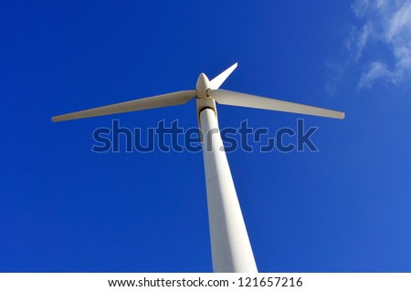 view of a wind turbine over the blue sky - stock photo