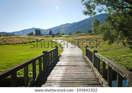 View of a wooden bridge leading to a golf field - stock photo