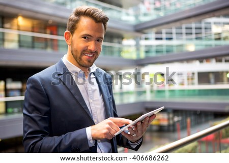 View of a Young attractive business man using tablet