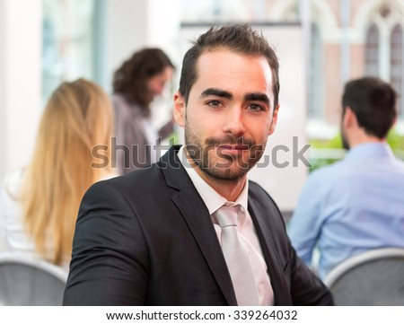 View of a Young attractive businessman working at the office with associates