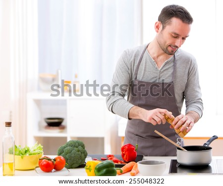 View of a Young attractive man cooking in a kitchen - stock photo
