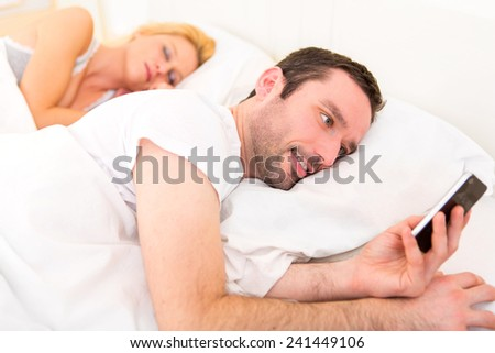 View of a Young attractive man sending text in a bed