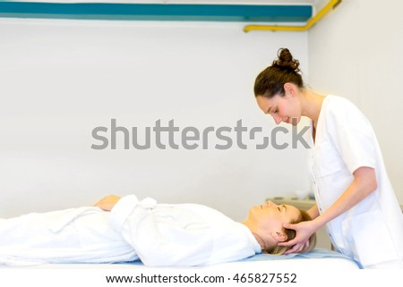 View of a Young attractive masseuse doing a capillariy massage