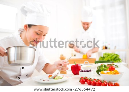 View of a Young attractive professional chef cooking in his kitchen  - stock photo