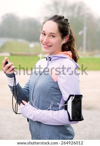 View of a Young attractive woman checking a chronometer durng a running session - stock photo