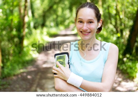 View of a Young attractive woman setting her mobile in armband before running - stock photo