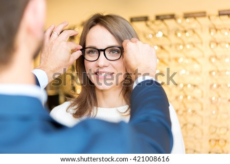 View of a Young attractive  woman testing new glasses with optician - stock photo