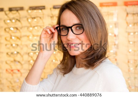 View of a Young attractive woman trying glasses at the optician - stock photo