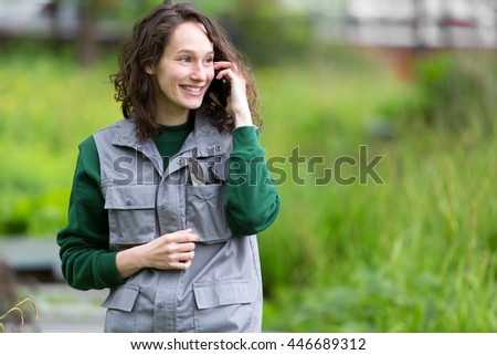 View of a Young attractive woman working in a public garden using mobile