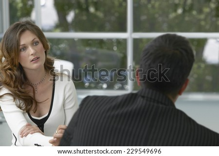 View of a young businesswoman talking to a colleague - stock photo
