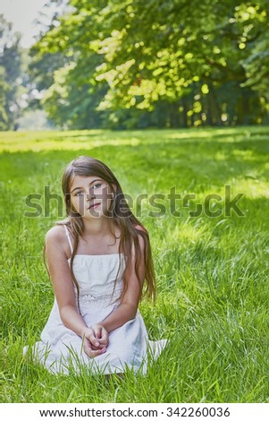 View of a young girl sitting on the grass