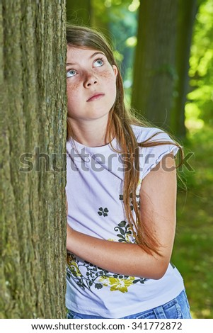View of a young girl standing near a tree trunk
