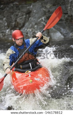 View of a young man kayaking in rough river - stock photo