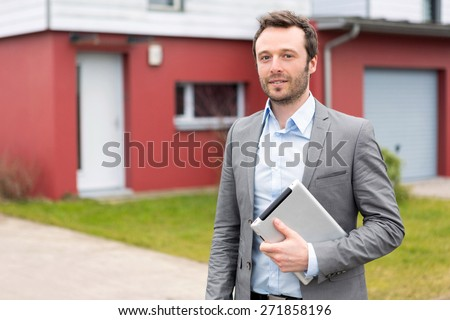 View of a young real estate agent in front of a house - stock photo