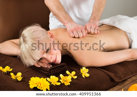 View Of A Young Woman Receiving Back Massage From A Massager In A Beauty Spa - stock photo
