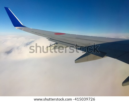 view of Airplane wing from window over blue sky.  Airline Transportation and Travel in japan.Take by Smartphone.