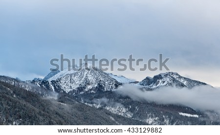 View of Alps mountain peaks and slow moving thick clouds around them with foothills in foreground during winter season - stock photo