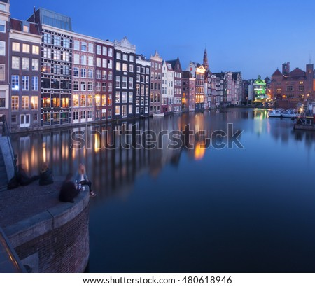 View of Amsterdam, netherlands, at dusk, with building's reflections on the canal.