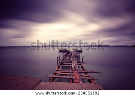 view of an abandoned pier taken with long exposure before rain/time is up - stock photo