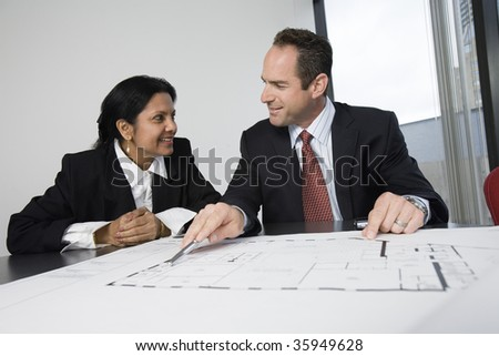 View of an architect smiling with a businesswoman. - stock photo