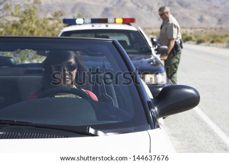 View of an Asian woman sitting in car being pulled over by police officer on desert road - stock photo