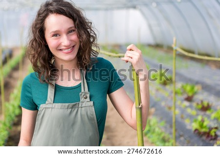 View of an attractive farmer in a greenhouse  - stock photo