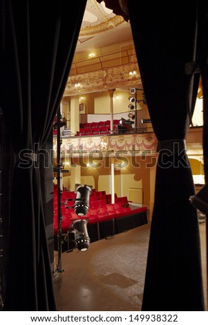 View of an empty stage with spotlights and red seats - stock photo