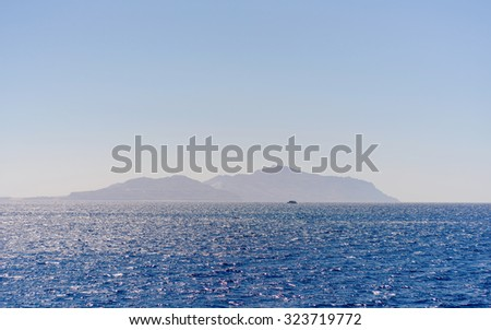 View of an idyllic tropical island rising from a calm blue ocean under a clear sunny blue sky - stock photo