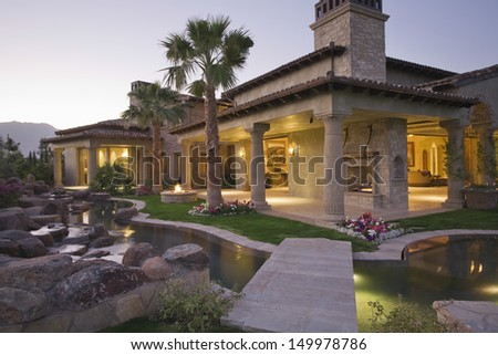 View of an illuminated modern house with pond in foreground - stock photo