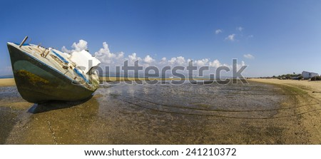View of an old abandoned boat stranded on dry sand at the beach. - stock photo
