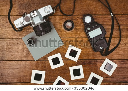 View of an old camera with photos slides on wood desk - stock photo