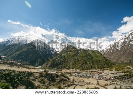 View of Annapurna II mountain (7,937 m) and Pisang village. Nepal, Himalayas. Annapurna II is a part of Annapurna circuit trek, one of the most popular adventure circuit trek in the world. - stock photo