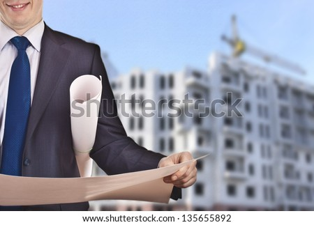 view of architect looking comparing housing project on being built multistory apartment background - stock photo