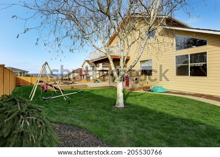 View of backyard with wooden walkout deck with patio area and kids playground - stock photo