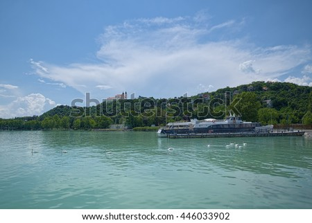 View of Balaton lake coast, Hungary, with Benedictine Tihany Abbey on top of green hill; a typical touristic ship is tied to pier, and white swans are floating around. - stock photo