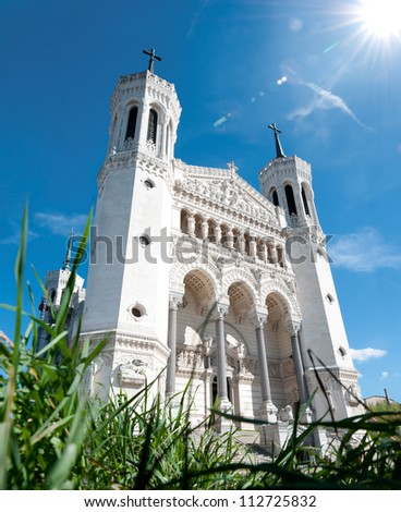 View of Basilica of Notre Dame de Fourvi���¨re (Fourviere) on a sunny day. Green grass in foreground and blue sky with sun and clouds in background. Lyon, France, Europe. - stock photo